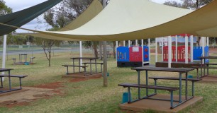 Photo of Min security visits area, picnic tables on grass under shade sails