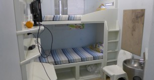Photo of a double bunk bed cell with a chair and toilet