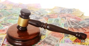 A judges gavel sitting on top of spread out Australian dollars