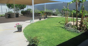 Image of the Gardens, with a shade sail over a BBQ and seating area within the Assisted Care Unit
