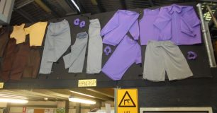 Production of prison clothing, displayed on boards above door in the textiles workshop