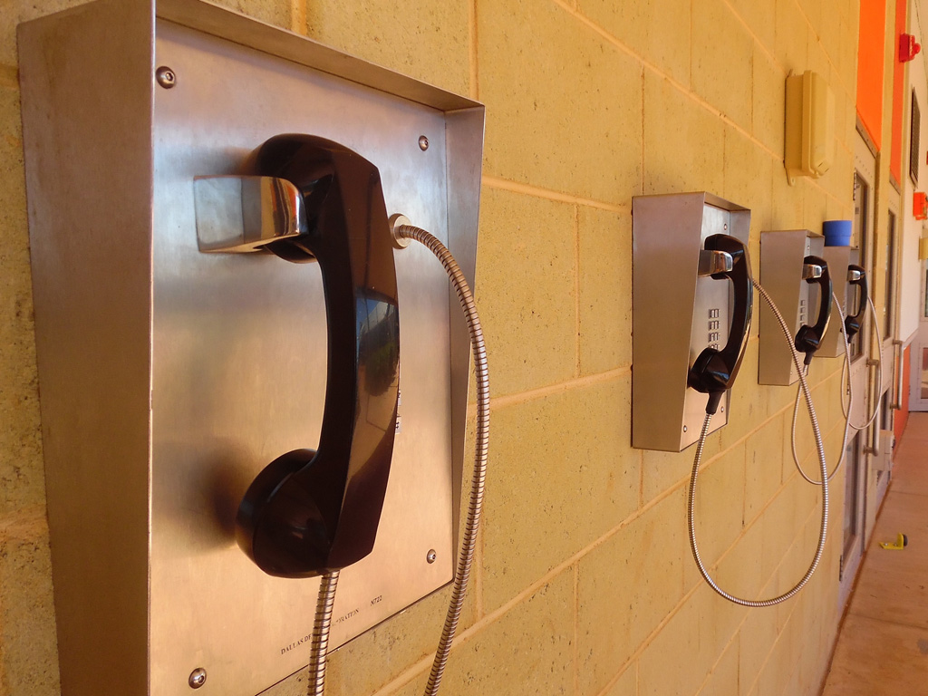 Four prisoner phones on a wall in prison